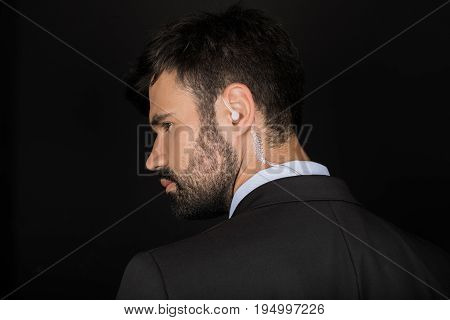 Secret Service Agent In Suit Using Earphone, Isolated On Black