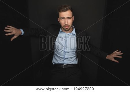 Handsome Businessman Posing In Black Suit, Isolated On Black