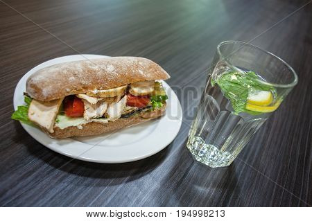 Sandwich with chicken and vegetables on a plate and a glass of water with mint and lemon on a table in a cafe