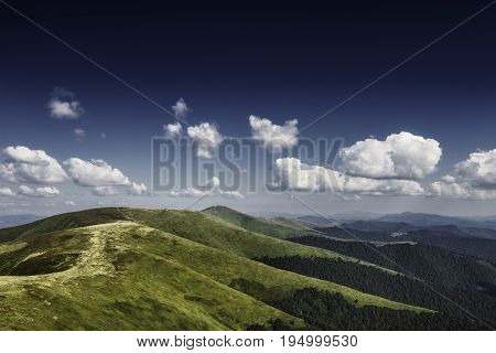 Autumn landscape. Autumn view of green Carpathian Mountains , Mountain road goes on top of the green hills on sunset landscape