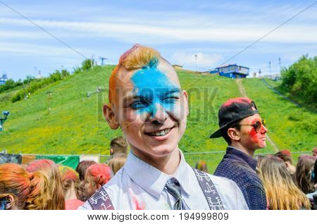 Moscow, Russia - June 3, 2017: Portrait of a smiling european teenage guy in a white shirt and face in blue paint after a headshot at a fun summer event Holi Colour Festival