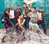 The studio shot of group of retro dancers posing at carnival tinsel. Concept of cabaret, luxury party and jazz poster