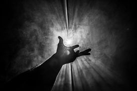 Hand reaches out to hold and touch the light