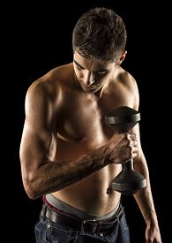 Shirtless bodybuilder exercising biceps curl isolated on black background