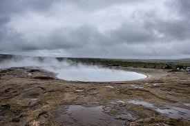 Natural Hot Springs geyser in Iceland. Steam rises from the Icelandic hot springs on a gloomy summer day