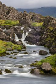 Waterfall shot with a long exposure method to generate motion blur effect with grass and rocks