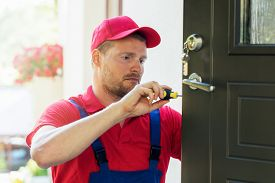 locksmith in red uniform installing new house door lock