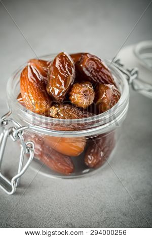 Dried Dates In A Glass Jar On A Light Grey Marble Table.