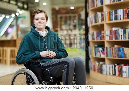 Content Handsome Young Disabled Student With Headphones On Neck Siting In Wheelchair And Looking At