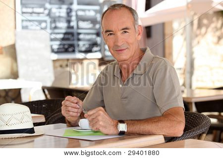 Older man drinking an expresso outside a cafe
