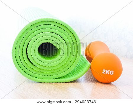 Woman Rolling Her Yoga Mat After A Workout - Top View.healthy Life, Keep Fit Concepts.equipment For