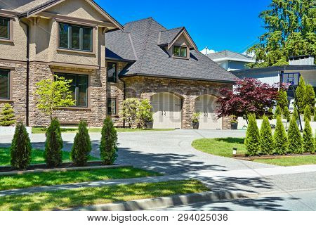 Fragment Of Luxury House With Double Garage And Concrete Driveway In Front. Front Yard Of Luxury Fam