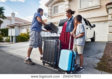 hispanic family packing luggage into pickup truck in front of house