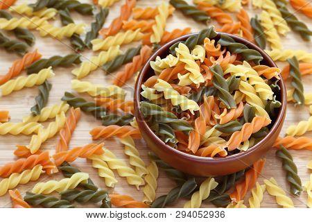 Raw Colorful Fusilli Pasta In A Bowl. Close-up.