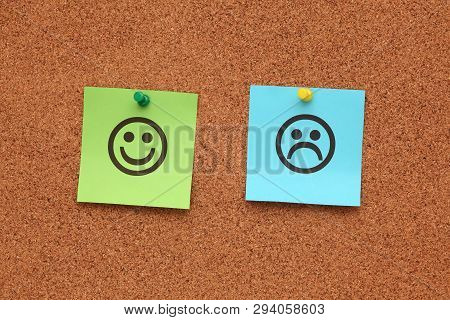 Green and blue paper with happy and sad faces on corkboard (bulletin board). poster