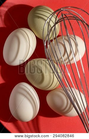 Shadows Pattern Of Raw Eggs And Metal Whisk