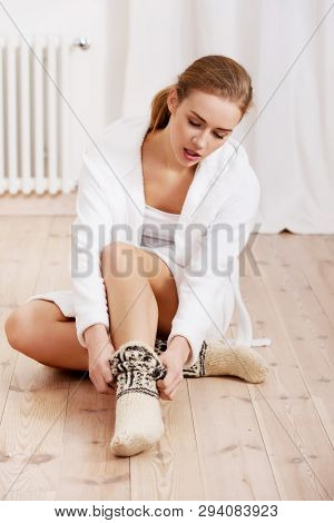 Young woman putting woolen socks on feet while sitting on floor, in home.