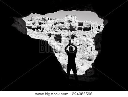 Silhouette Of Man Figure In Natural Rock Background.man Photographer Taking Photos In The Middle Of