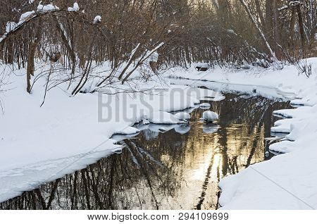 Snowy Banks Of Minnehaha Creek Flowing Through Woodlands Of Minnehaha Parkway And Sun Reflecting Off