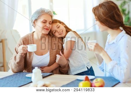 Happy Family Three Generations   Grandmother, Mother And Child Hugging In The Kitchen At Home