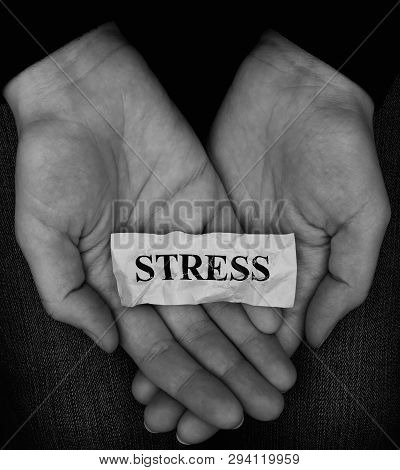 Woman Holding Word Stress In Her Palms. Black And White Image. Close Up.