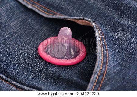 Pink Condom On Blue Jeans Pocket. Close Up