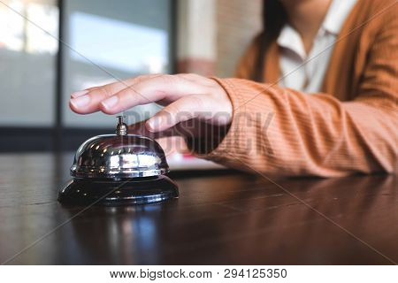 Women Call Hotel Reception With Finger Push A Bell In Lobby Hotel. Hotel Concept.