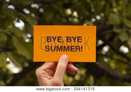 Bye, Bye Summer! Hand Holds Yellow Piece Of Paper That Says Bye, Bye Summer!. Close Up.