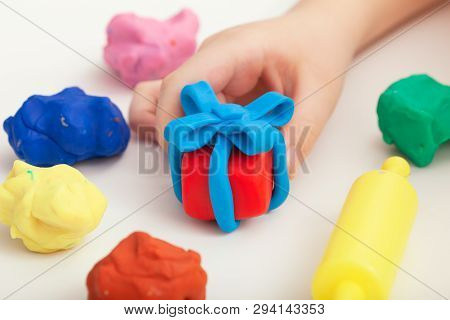 Child Playing With Playdough And Making A Giftbox. Close Up.