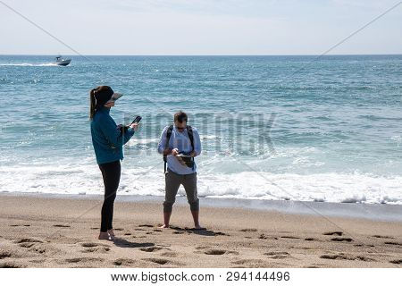 Malibu, California - March 26, 2019: Adult Tourists Fuss And Play With Their Phones While Enjoying T