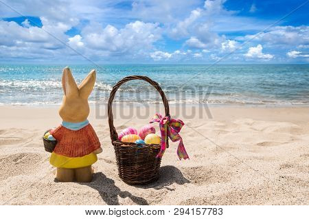 Easter Bunny With Color Eggs On The Sandy Beach Near Ocean