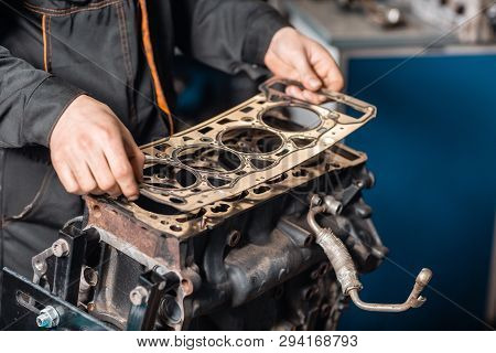 Sealing Gasket In Hand. The Mechanic Disassemble Block Engine Vehicle. Engine On A Repair Stand With