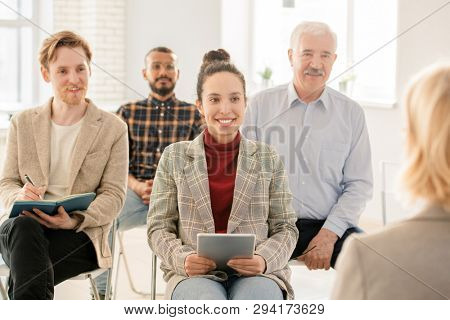 Happy young mixed-race woman and other students looking at their teacher while listening to her and making notes at seminar