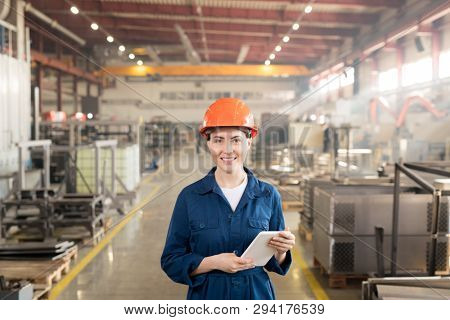 Happy female engineer in helmet and overalls looking at you while working inside large industrial plant