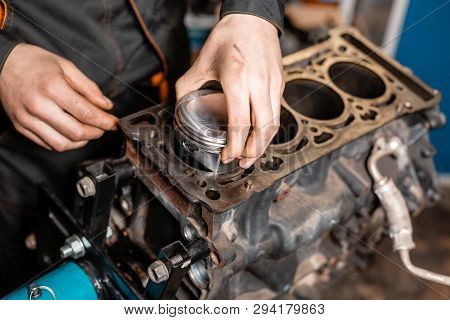 Close-up Car Mechanic Holding A New Piston For The Engine, Overhaul.. Engine On A Repair Stand With