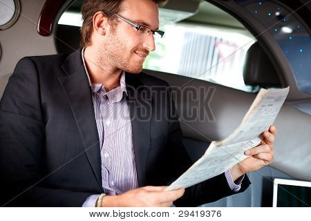 Elegant young man reading newspaper in luxury car.?