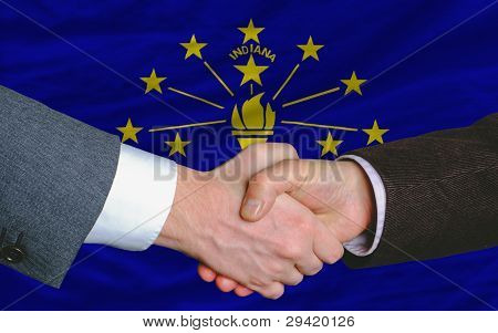In Front Of American State Flag Of Indiana Two Businessmen Handshake After Good Deal