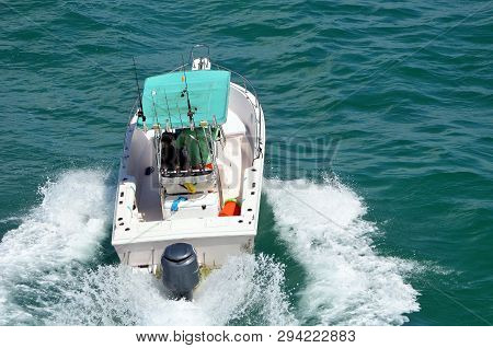 Angled Overhead View Of An Open Sport Fishing Boat With A Aqua Colored Canvas Canopy Powered By A Si