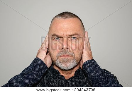 Determined man covering his ears with his hands to block out something he does not wish to hear or in a concept of hear no evil staring at the camera on a grey background poster