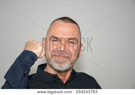 Victorious stylish man raising a fist in jubilation with a happy smile of success over a grey studio background poster