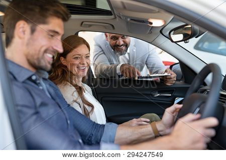 Cheerful young couple looking around in new car at showroom while car dealer explaining the features. Mature couple choosing car in car dealrship. Happy man and beautiful woman looking inside the auto