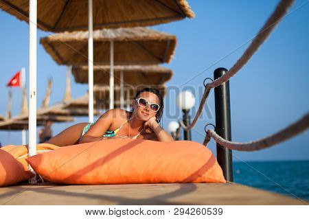 Girl Lying On The Pier. Attractive Young Woman In Swimsuit Lying On The Pier. Woman In Swimsuit Lyin