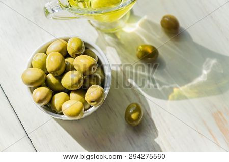 Top View Of Glass Sauceboat With Extra Virgin Olive Oil And Fresh Green Olives  On Wooden Table.