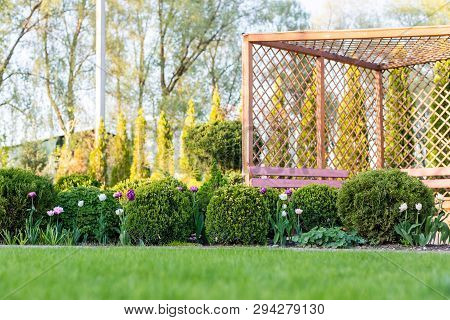 Beautiful Green Garden With Frsesh Boxwood Bushes, Flowers And Wood Grating Summerhouse.scenic Summe