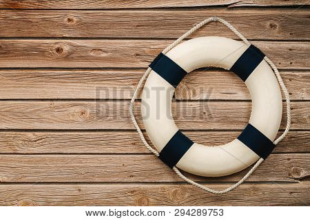 Close Up Of Life Buoy On The Wooden Background With Copy Space