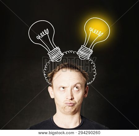 Man With Light Bulb On Blackboard Background. Brainstorming And Idea Concept