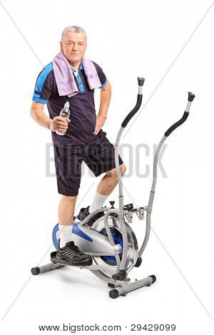 Senior man holding a water bottle and standing on a cross trainer machine, isolated on white background