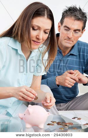 Senior couple with money and piggy bank on table