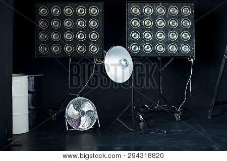 Studio setup on a black background, studio flash, fan. poster