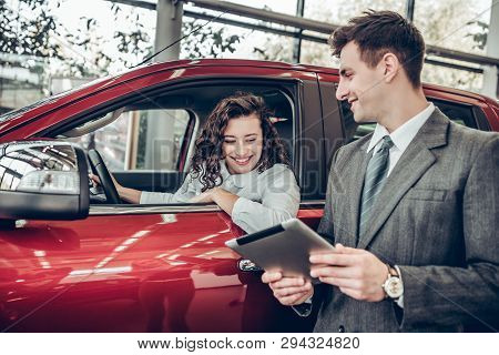 Car Info. Happy Young Woman Sitting In A New Car At Car Salon Professional Salesman Showing Them Inf